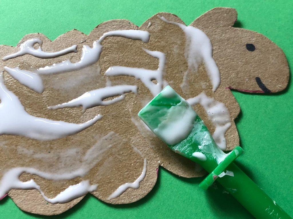 Put glue onto sheep cut out